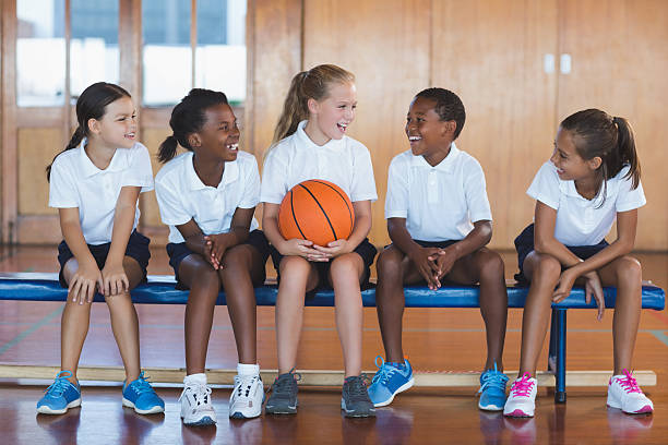 School kids having fun in basketball court stock photo