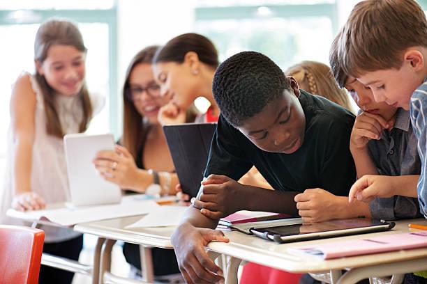School kids in class using a digital tablet - foto de acervo