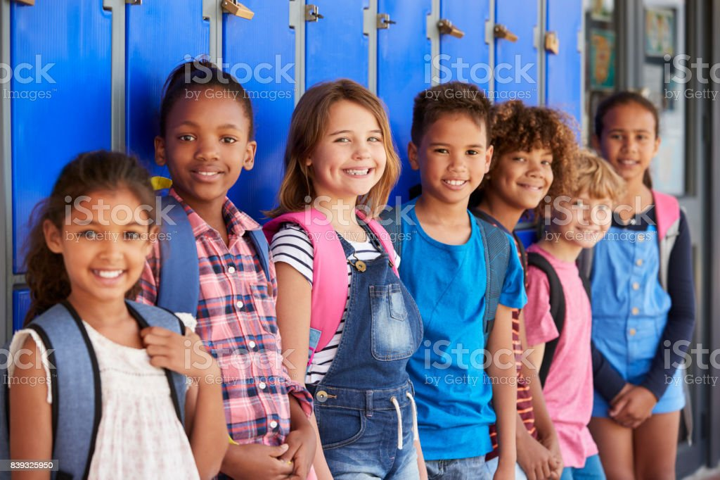 Niños de la escuela frente de armarios en el pasillo de la escuela primaria - foto de stock
