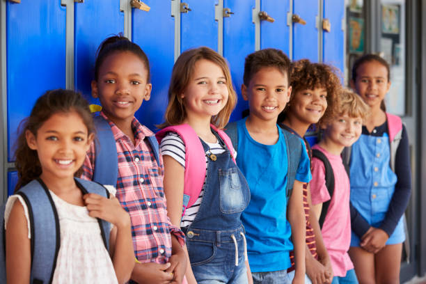 School kids in front of lockers in elementary school hallway stock photo