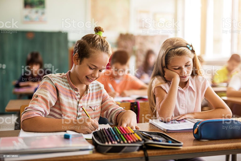 School kids learning during lecture in the classroom. stock photo