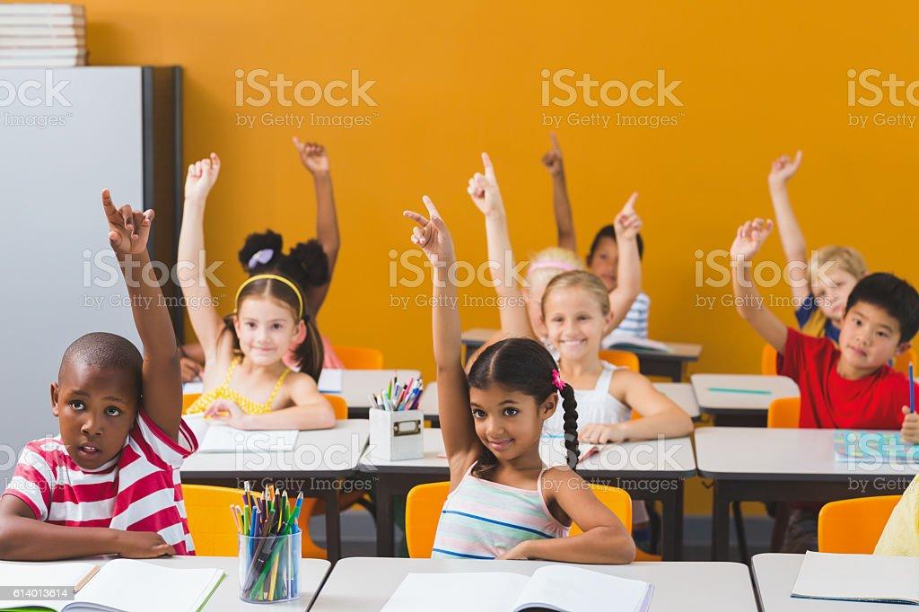 School kids raising hand in classroom - foto de stock
