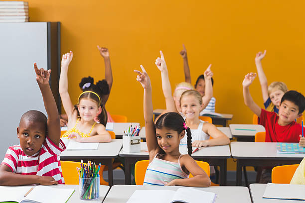 School kids raising hand in classroom stock photo