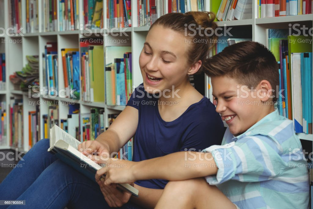 School kids reading books in library at school stock photo
