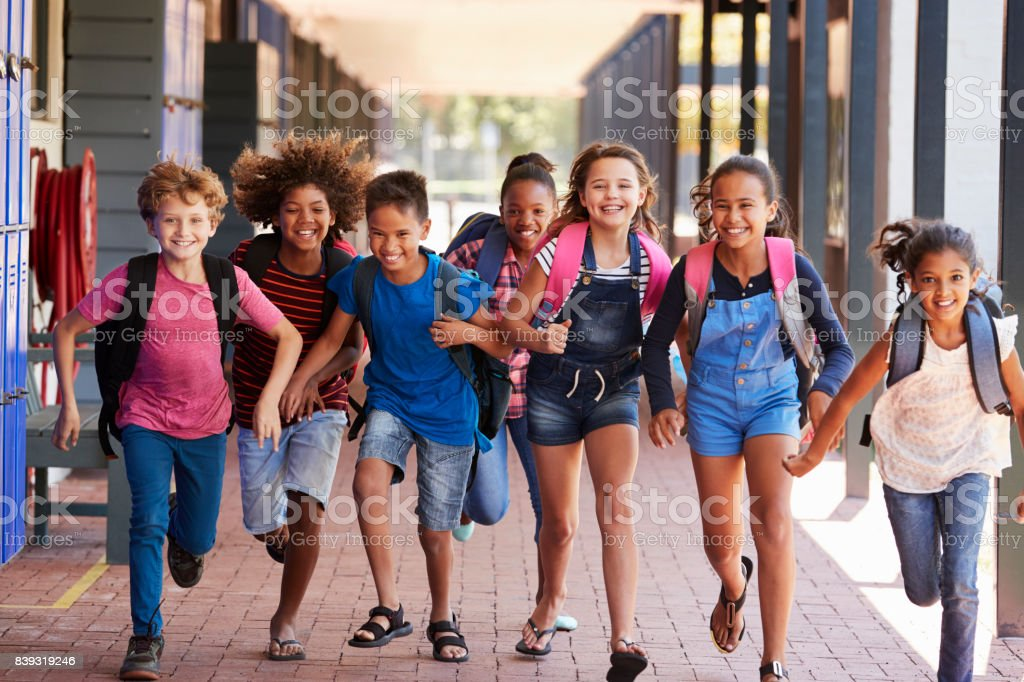 064a9a81b30 School kids running in elementary school hallway, front view - Stock image .