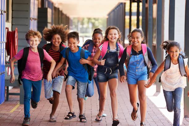 schulkinder laufen in grundschule flur, vorderansicht - kind vor der pubertät stock-fotos und bilder