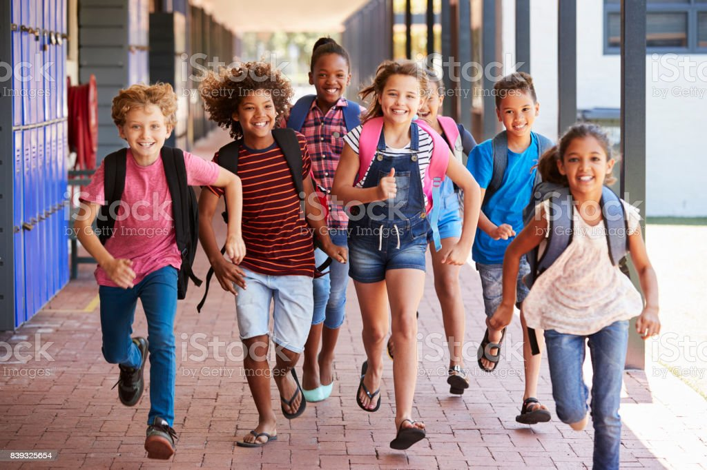 School kids running in elementary school hallway, front view stock photo