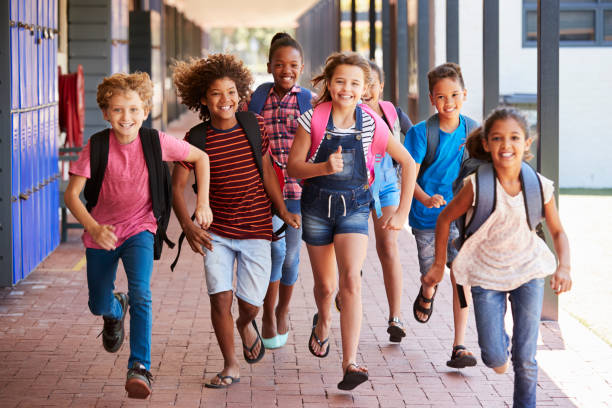 school kids running in elementary school hallway, front view - school building stock photos and pictures