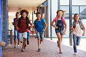 istock School kids running in elementary school hallway, front view 839326854