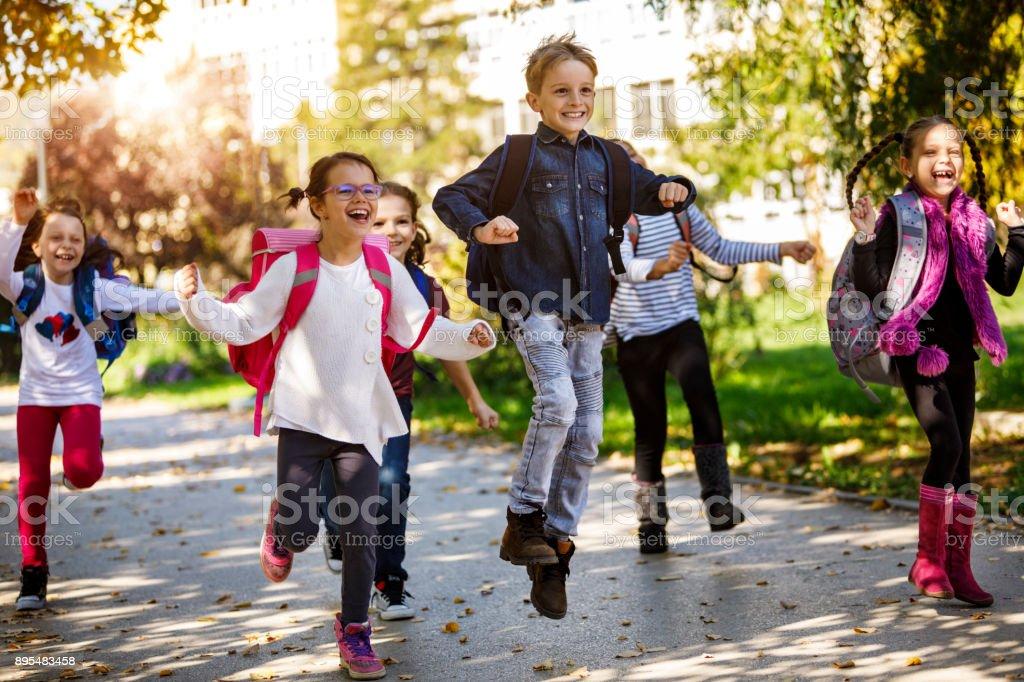 School kids running in schoolyard stock photo