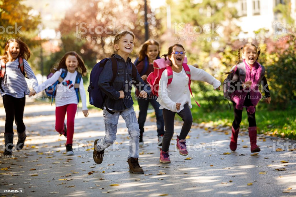 School kids running in schoolyard stock photo