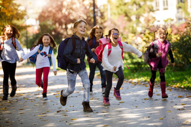 school kids running in schoolyard - school building stock photos and pictures