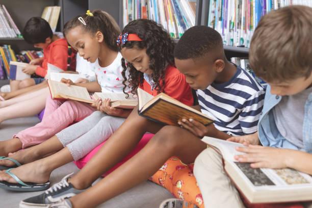 scolari seduti su cuscini e che studiano libri in una biblioteca - bambino foto e immagini stock