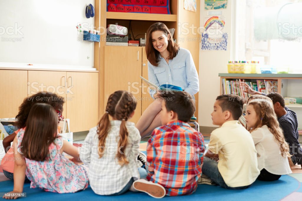 School kids sitting on floor in front of teacher, low angle foto stock royalty-free