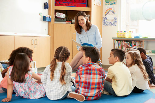School kids sitting on floor in front of teacher, low angle