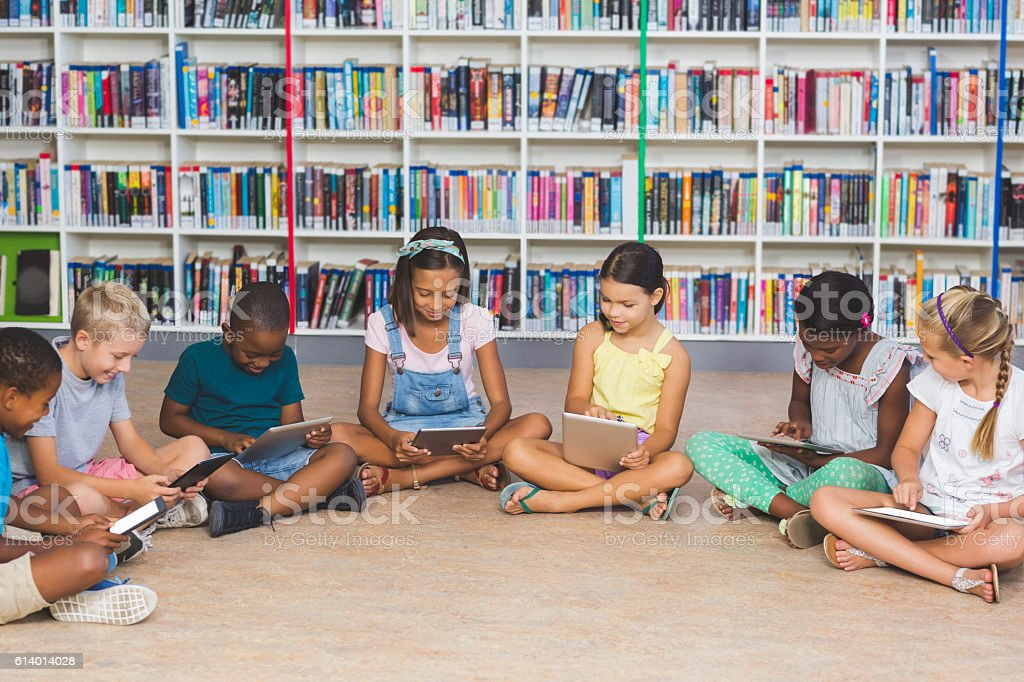 School kids sitting on floor using digital tablet in library stock photo