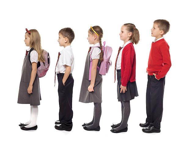 School Kids Standing In Line, Studio Isolated stock photo