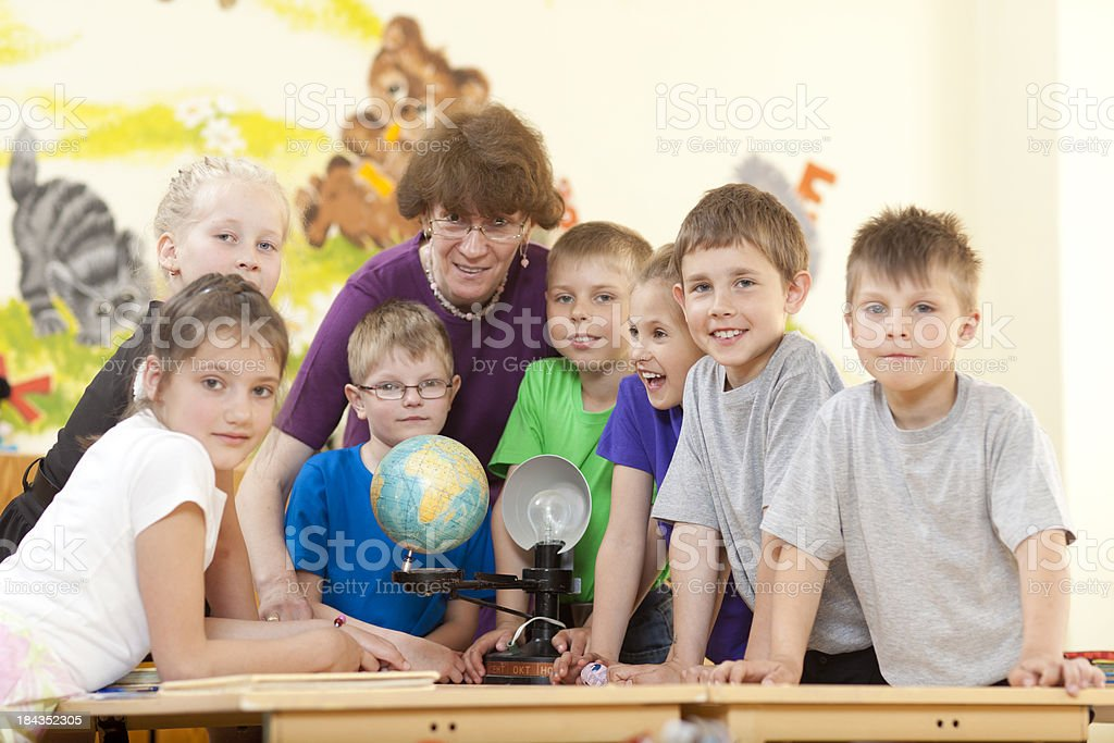 School kids together with their teacher smiling stock photo
