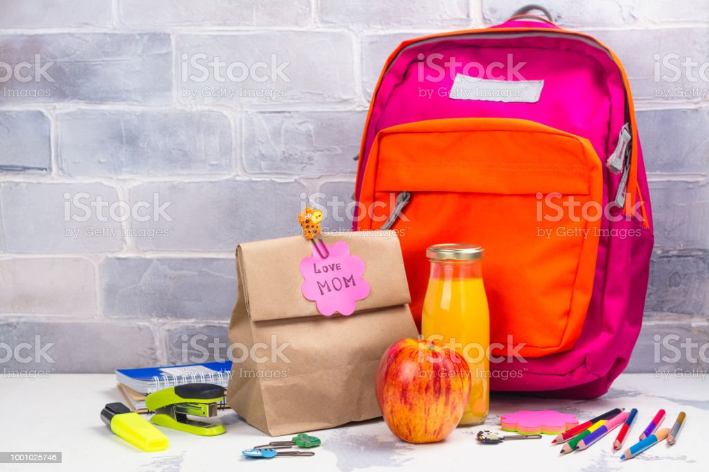 School lunch box and pink backpack stock photo