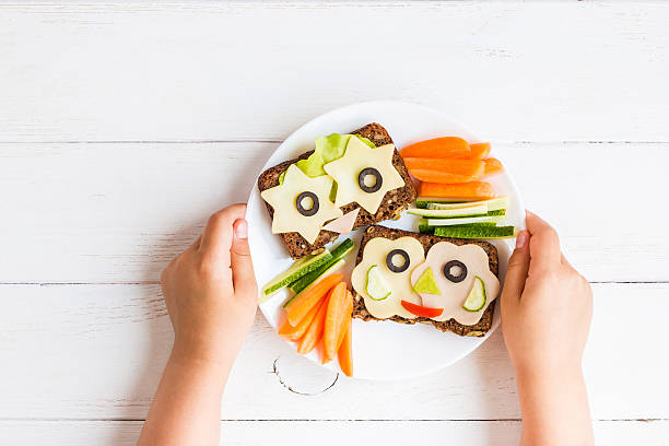 school lunch box for kids. child's hands. flat lay - käse wurst salat stock-fotos und bilder