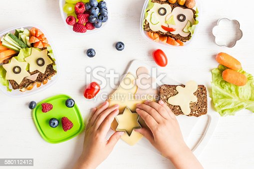School lunch box for kids. Cooking. Child's hands. Top view, flat lay