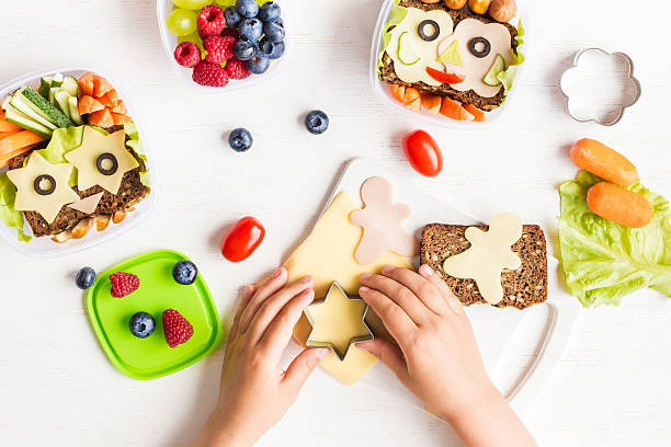 school lunch box for kids. cooking. child's hands. flat lay - käse wurst salat stock-fotos und bilder