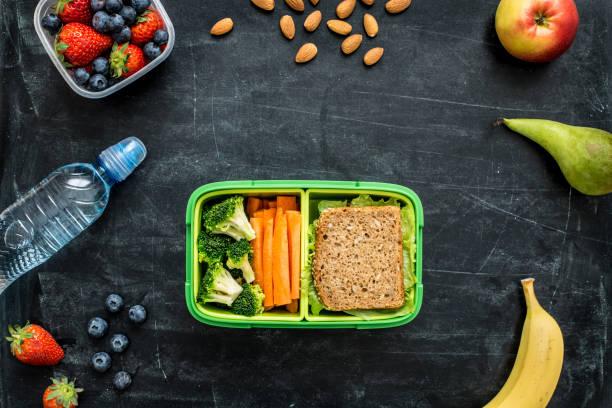 schulmittagsbox mit sandwich, gemüse, wasser und obst - mittagspause schild stock-fotos und bilder