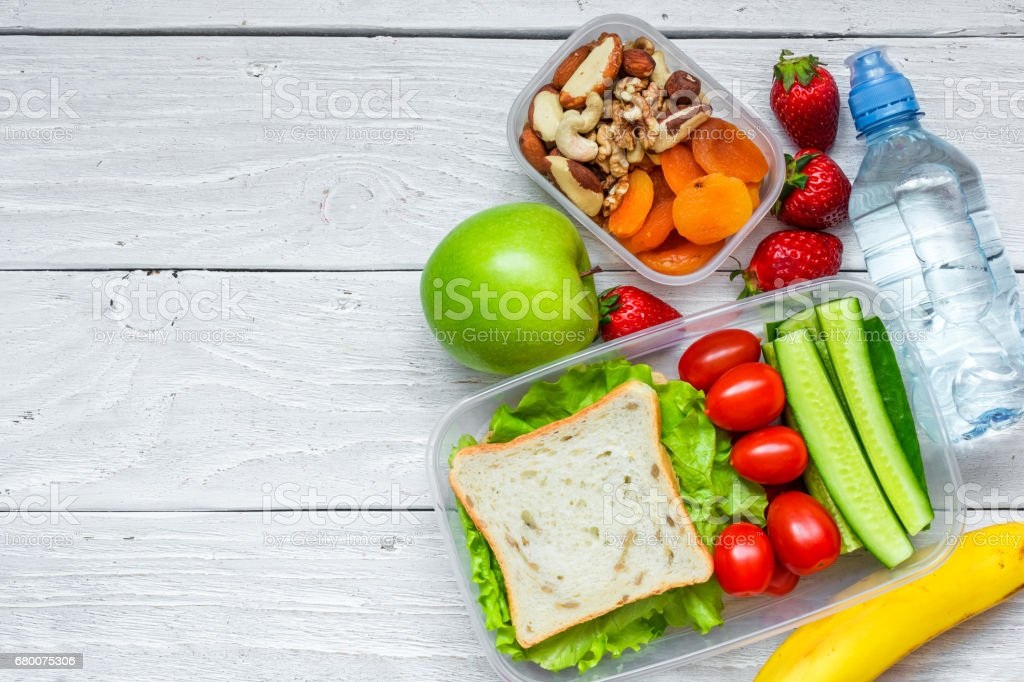 school lunch boxes with sandwich and fresh vegetables, bottle of water, nuts and fruits stock photo