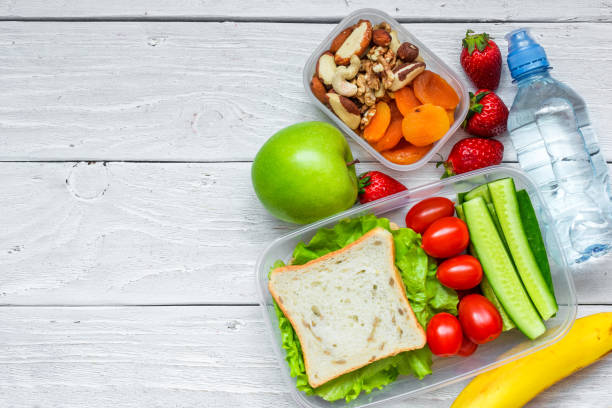 school lunch boxes with sandwich and fresh vegetables, bottle of water, nuts and fruits - foto stock