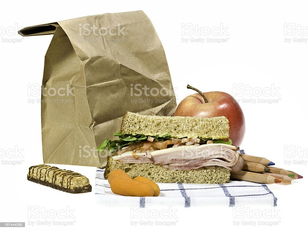 School lunch next to brown paper bag on a white background royalty-free stock photo