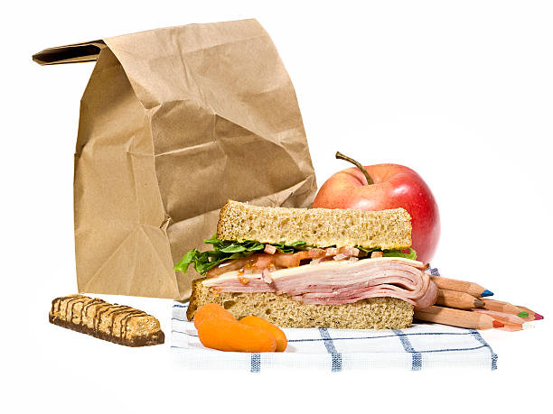 School lunch next to brown paper bag on a white background stock photo