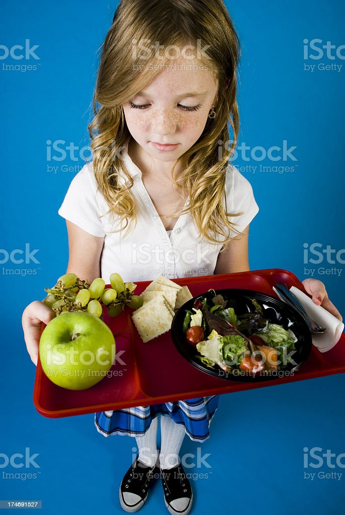 School Lunch Young school girl studying her healthy lunch Adolescence Stock Photo
