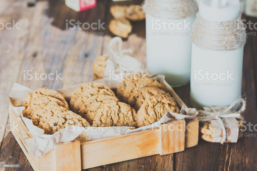 School milk bottles and oatmeal cookies on wooden background stock photo
