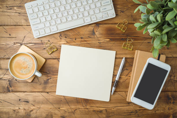 School notebook with coffee cup, smartphone and plant on wooden table. Top view from above stock photo