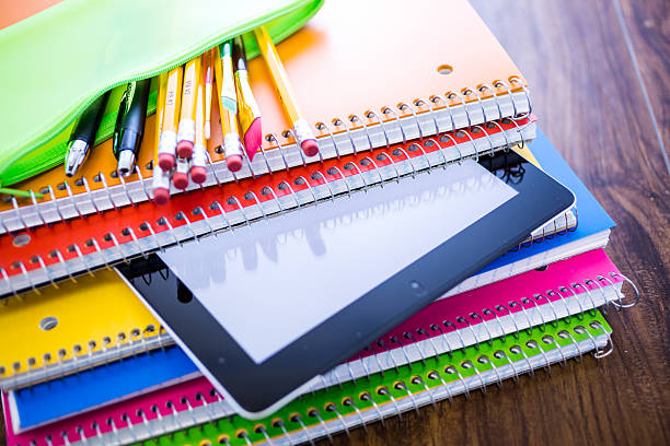 School notebooks in variety of colors with pencils in bag stock photo