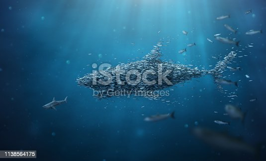 Stronger together concept image of underwater scene with smaller fish forming and taking shape of bigger shark chasing away a shark.