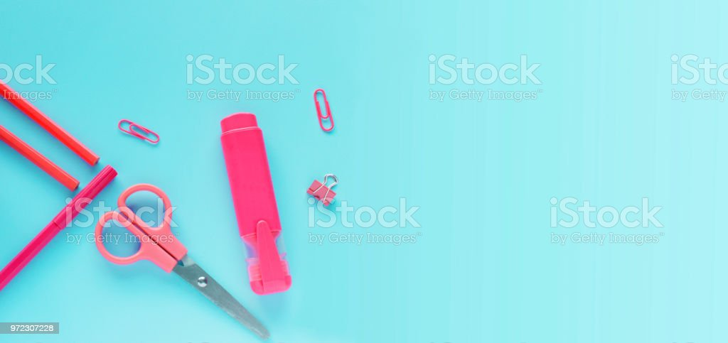 School or office pink supplies on blue background. Back to school concept, flat lay. Copy spase stock photo