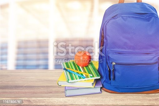 Blue school backpack with school supplies on wooden table