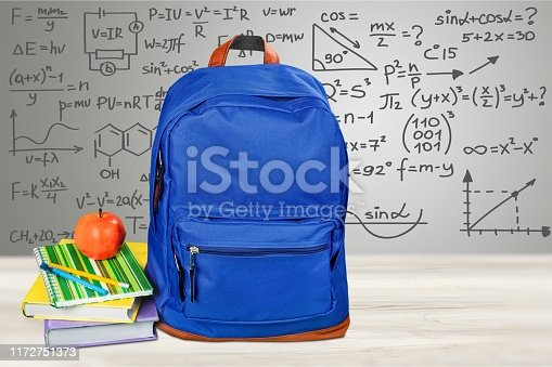 School blue backpack with stack book and apple