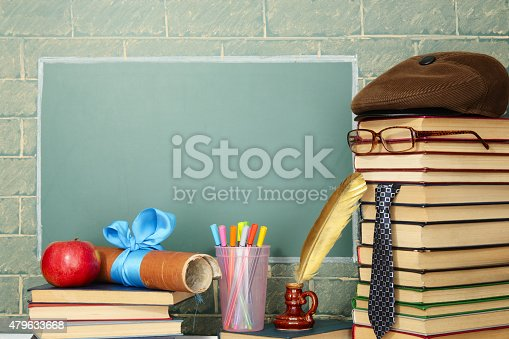Unusual jesting teacher, books, quill, pen, scroll, apple before blackboard with copy space