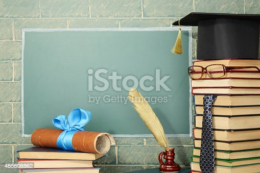 Unusual jesting teacher, books, quill pen, scroll before blackboard with copy space
