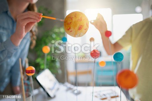 Mother and her boy enjoy making a solar system model for his school homework project.