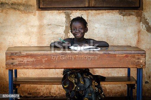 istock School: Proud African Schoolgirl Sitting In Her Desk Smiling 520408073