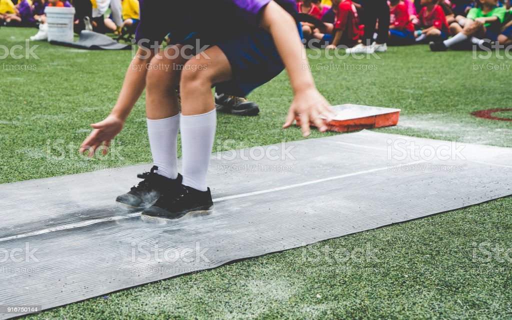 Students boy taking long jump on rubber board pid or sand pid during...