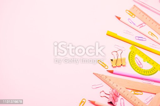 istock School statinery flat lay on pink background. 1131376678