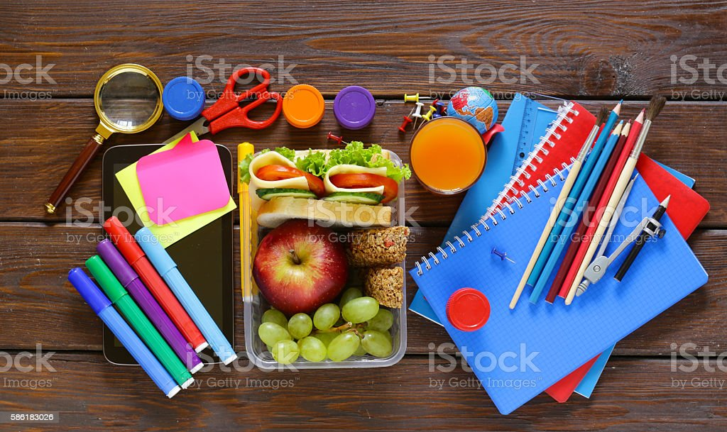 school stationery and lunch box with apple, grapes and sandwich stock photo