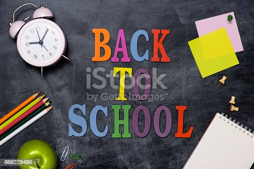 istock School stationery or office supplies on chalkboard background. 666229486