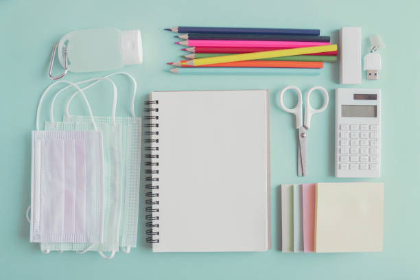 school stationery supplies, medical masks and hand gel sanitizer, school reopening, returning back to school after covid-19 coronavirus pandemic is over, new normal concept - new normal foto e immagini stock