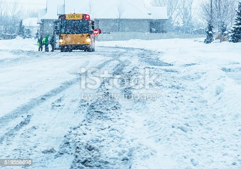 A line of anonymous school children students waiting to board a bright yellow school bus with open door, flashing red lights and outstretched warning stop sign during a raging winter blizzard snow storm on a slippery, slushy, tire track criss-crossed suburban residential street.