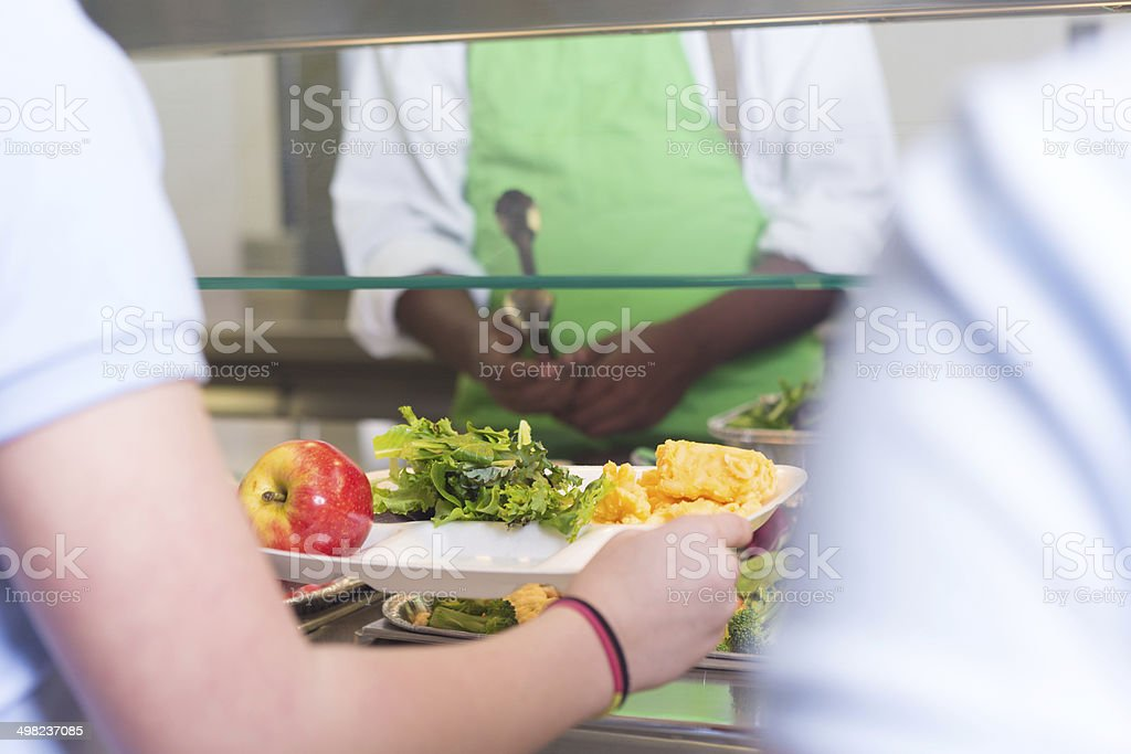 School students choosing variety of healthy foods in lunch line stock photo